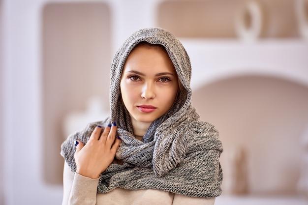 Portrait de jeune femme européenne avec un foulard sur la tête à l'intérieur