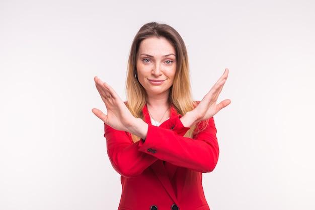 Portrait de jeune femme européenne en rouge jacked en studio avec les mains croisées.