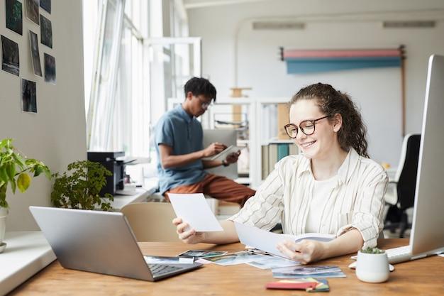 Portrait de jeune femme examinant des photographies tout en travaillant sur l'édition et la publication dans un bureau moderne, copiez l'espace