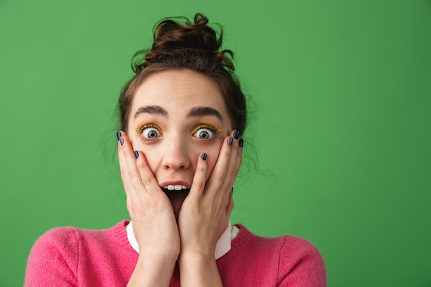 Portrait d'une jeune femme excitée criant isolé sur vert