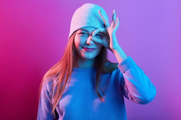 Portrait de jeune femme excitée habillée chandail décontracté et bonnet tricoté, montrant signe ok contre son œil