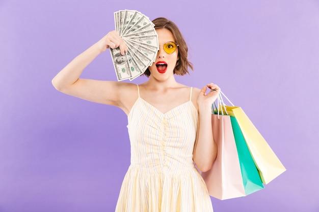 Portrait d'une jeune femme excitée à lunettes de soleil