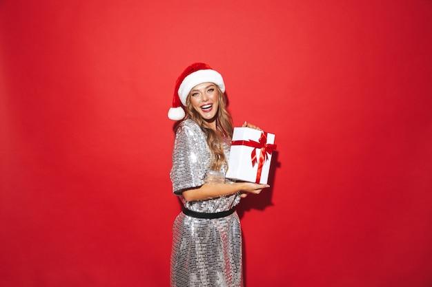 Portrait d'une jeune femme excitée portant un chapeau rouge célébrant le nouvel an isolé sur l'espace rouge