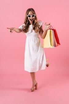 Portrait d'une jeune femme excitée portant des lunettes de soleil pointant le doigt de côté et tenant des sacs à provisions isolés sur un mur rose