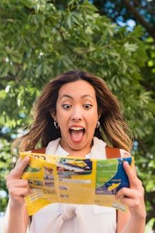 Portrait d'une jeune femme excitée en regardant une carte touristique