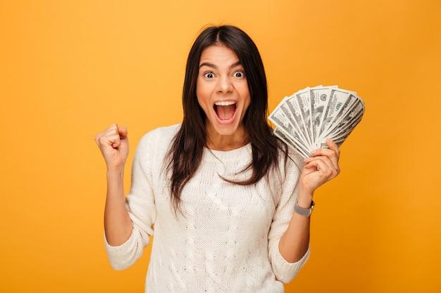 Portrait d'une jeune femme excitée tenant des billets d'argent