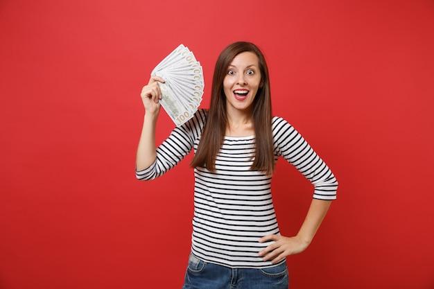 Portrait d'une jeune femme excitée en vêtements rayés tenant beaucoup de dollars, argent comptant isolé sur fond de mur rouge vif. les gens émotions sincères, concept de style de vie. maquette de l'espace de copie.