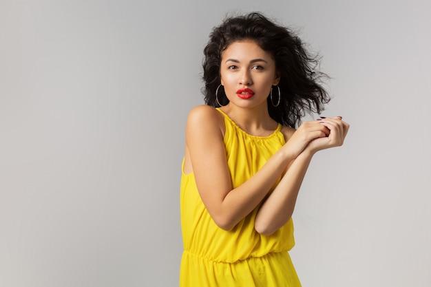 Portrait de jeune femme exotique attrayante en robe élégante jaune, lèvres rouges, aspect naturel, peau pure, souriant, isolé, style de saison estivale, tendance de la mode, vent dans les cheveux bouclés