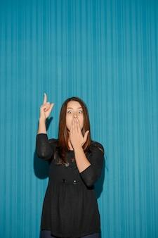 Portrait de jeune femme avec une expression faciale choquée sur fond bleu studio pointant vers le haut