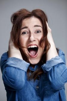 Portrait de jeune femme avec une expression faciale choquée