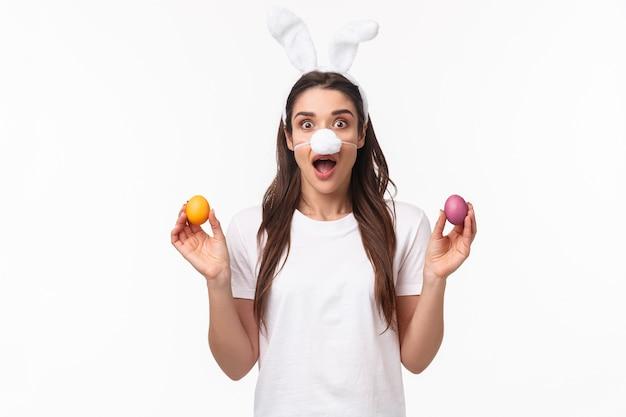 Portrait jeune femme expressive porter des oreilles de lapin et le nez, tenant des oeufs colorés