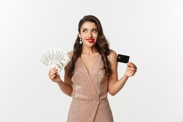Portrait jeune femme expressive en robe élégante tenant des billets en dollars et carte de crédit