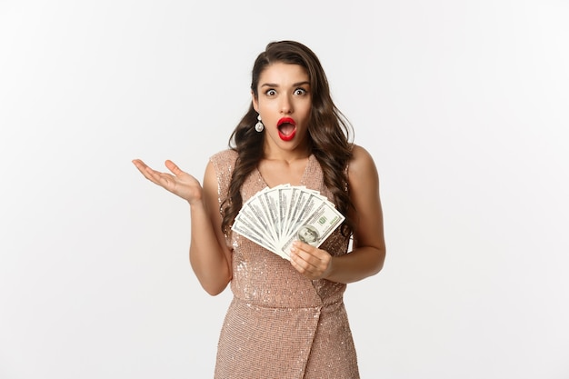Portrait jeune femme expressive en robe élégante tenant des billets en dollars