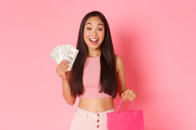 Portrait jeune femme expressive avec des sacs à provisions et de l'argent