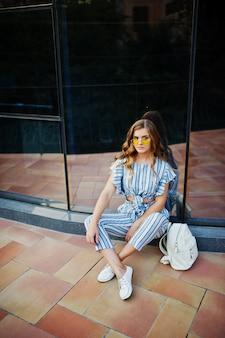 Portrait d'une jeune femme fabuleuse en combinaison rayée et lunettes de soleil assis sur le sol et posant