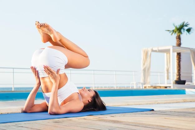 Portrait d'une jeune femme faisant des exercices de yoga en plein air