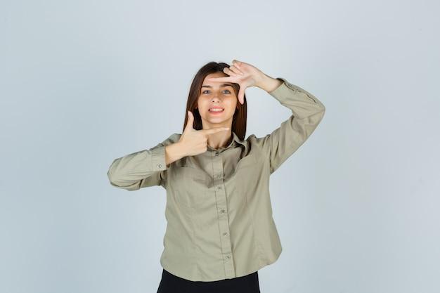 Portrait de jeune femme faisant un geste de cadre en chemise, jupe et à la vue de face heureuse