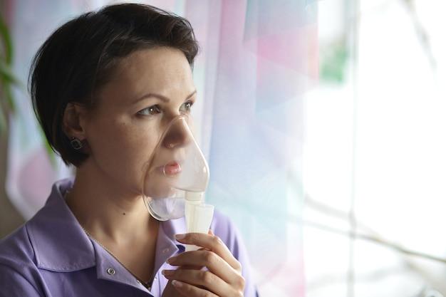 Portrait d'une jeune femme faisant l'inhalation à la maison