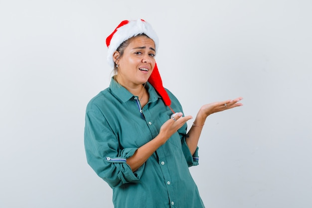 Portrait de jeune femme faisant semblant de montrer quelque chose en chemise, bonnet de noel et à la vue de face surpris