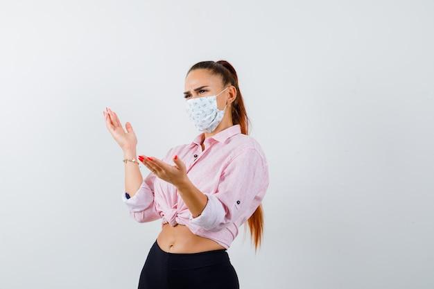 Portrait de jeune femme faisant semblant de montrer quelque chose en chemise, pantalon, masque et à la vue de face perplexe
