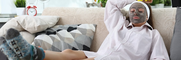 Portrait de jeune femme fatiguée reposant sur un canapé après un nettoyage actif à la maison. femme portant un masque facial d'argile. intérieur confortable dans le salon. pinceau jaune et chiffon. concept de loisirs