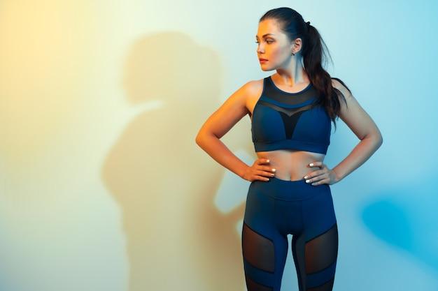Portrait d'une jeune femme fitness en vêtements de sport qui pose en studio