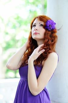 Portrait de jeune femme avec une fleur dans les cheveux.