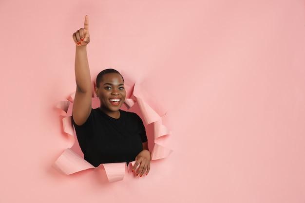 Portrait de jeune femme sur fond de rupture déchirée rose