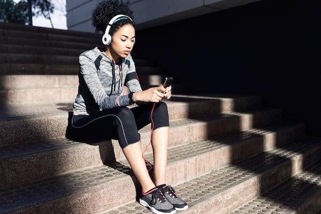 Portrait d'une jeune femme en forme et sportive écoutant de la musique avec un téléphone portable.