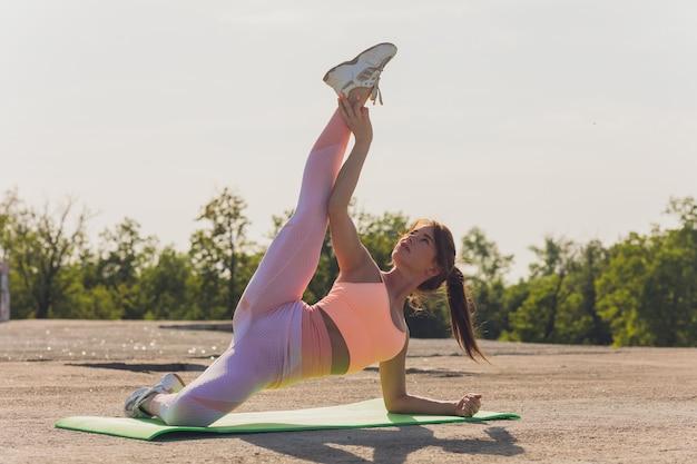 Portrait de jeune femme en forme et sportive faisant des étirements en ville.