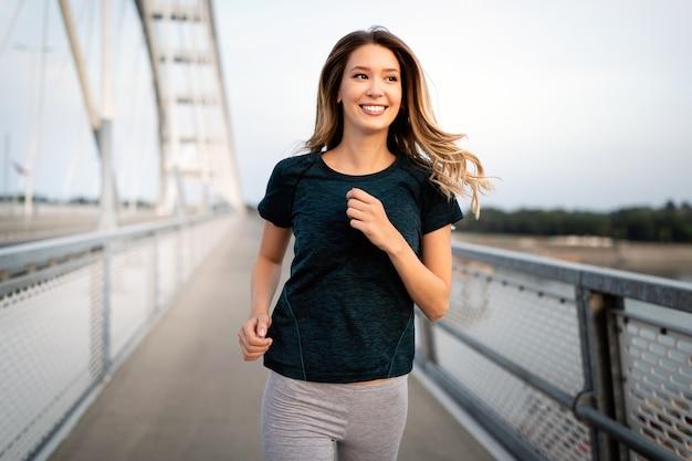 Portrait de jeune femme en forme et sportive qui court dans la ville