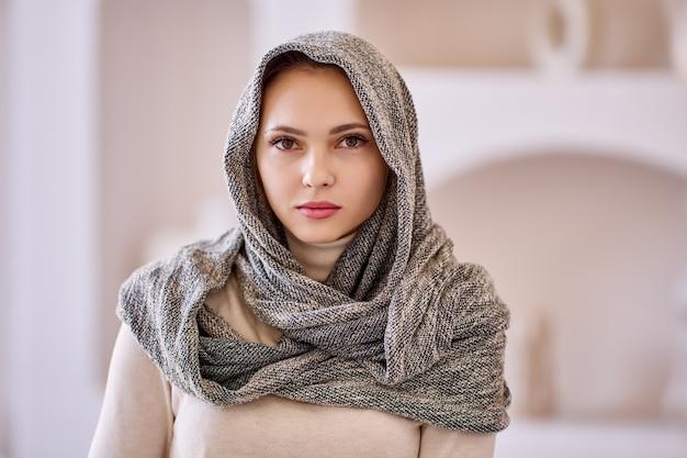 Portrait de jeune femme avec foulard à la maison
