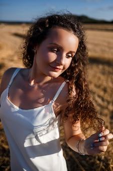 Portrait d'une jeune femme frisée dans un champ de blé, où le blé est fauché et les gerbes sont debout, profitant de la nature. la nature. rayons de soleil agriculture