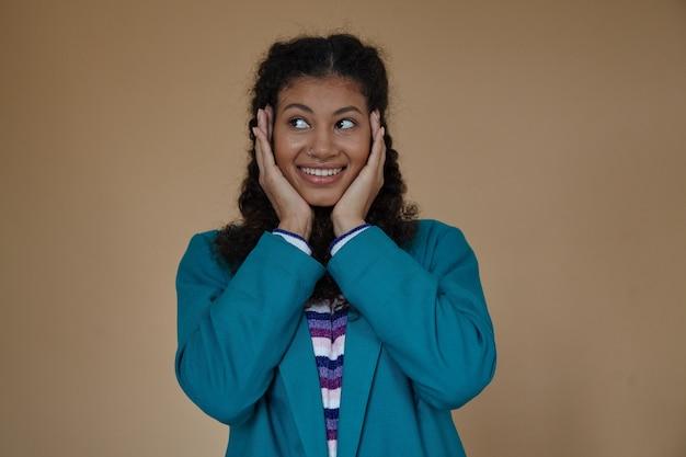 Portrait de jeune femme frisée à la peau sombre positive avec des tresses en gardant les paumes sur ses joues et à la joyeusement de côté avec un sourire sincère, isolé