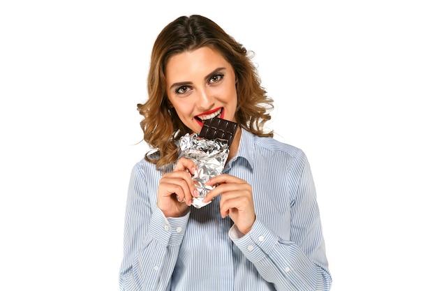 Portrait de jeune femme gaie, manger du chocolat noir savoureux enveloppé dans une feuille