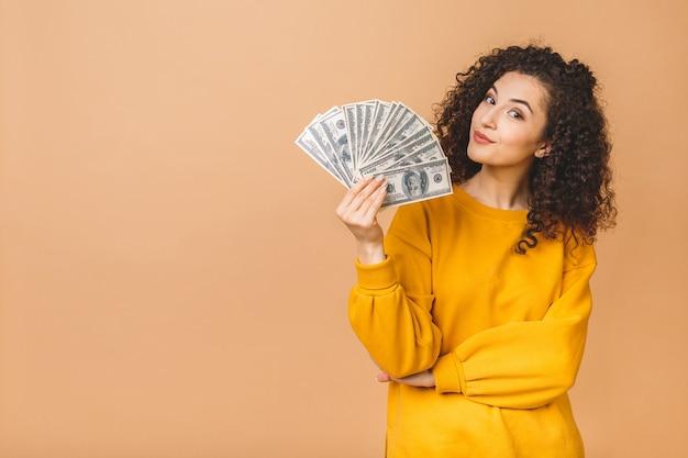 Portrait d'une jeune femme gaie tenant des billets en argent et célébrant isolé sur fond beige.