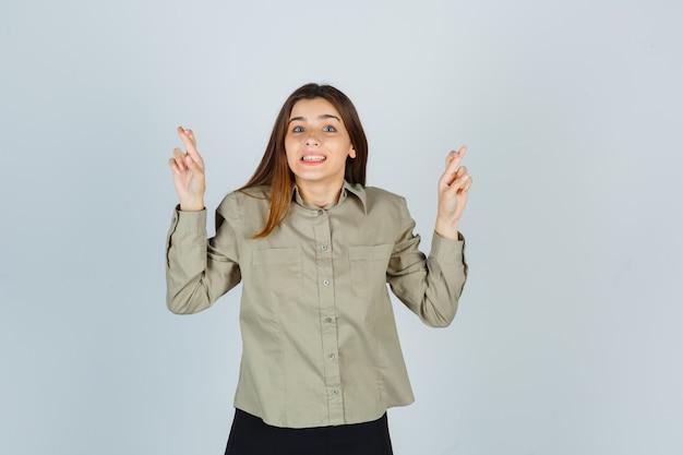 Portrait de jeune femme en gardant les doigts croisés en chemise