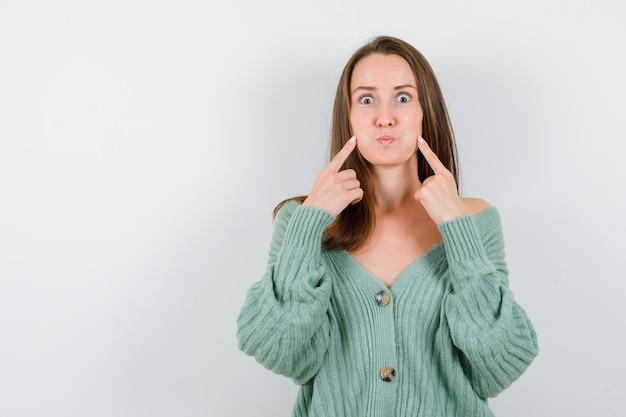 Portrait de jeune femme en gardant les doigts sur les joues soufflées en cardigan en laine et à la drôle de vue de face