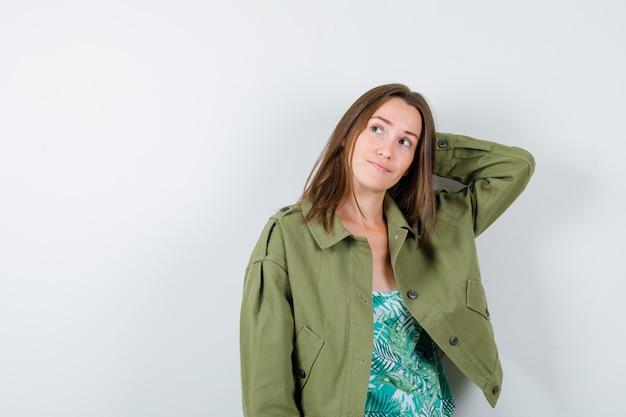 Portrait de jeune femme gardant la main derrière la tête en blouse, veste et à la vue de face pensive