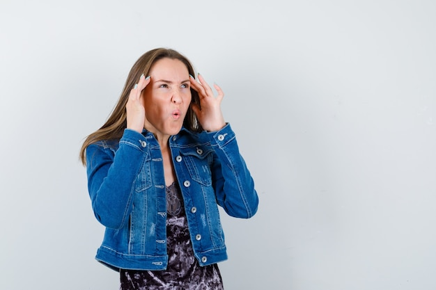 Portrait de jeune femme gardant la main sur les tempes, ouvrant la bouche en veste en jean, robe et regardant terrifié vue de face
