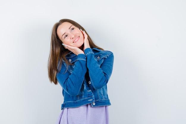 Portrait de jeune femme gardant les mains sur les joues, levant les yeux dans une veste en jean et regardant la vue de face de rêve