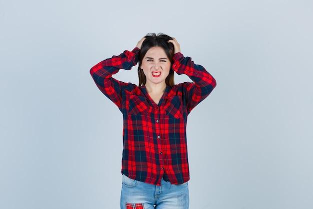 Portrait de jeune femme gardant les mains sur la tête en chemise à carreaux, jeans et à la vue de face ennuyée