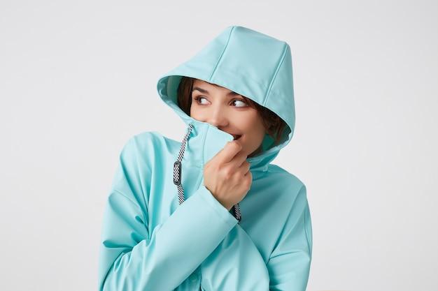Portrait de jeune femme gentille positive en manteau de pluie bleu, avec une capuche sur la tête, détourne le regard avec des expressions joyeuses, largement souriant, couvre son visage avec un collier, se dresse sur un mur blanc.