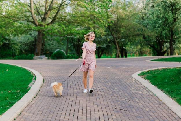 Portrait d'une jeune femme glamour vêtue d'une robe rose tenant son mignon spitz de poméranie sur les mains. . amitié entre chiens et humains.