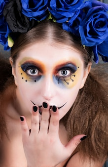 Portrait d'une jeune femme avec halloween composent avec des fleurs bleues.