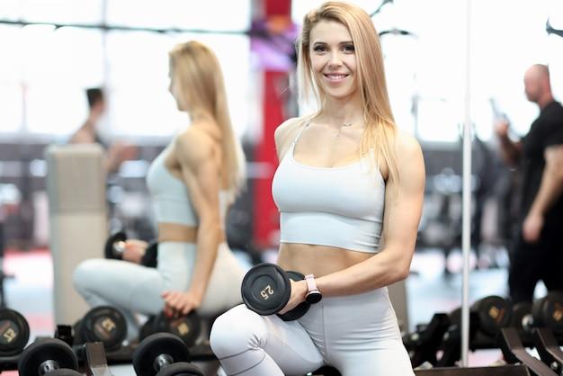 Portrait de jeune femme avec des haltères dans la salle de sport
