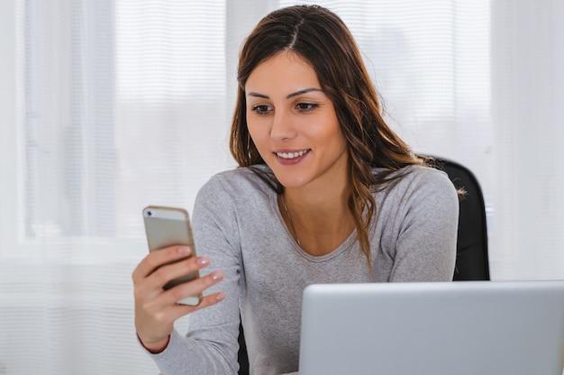 Portrait d'une jeune femme heureuse à l'aide d'un téléphone portable.