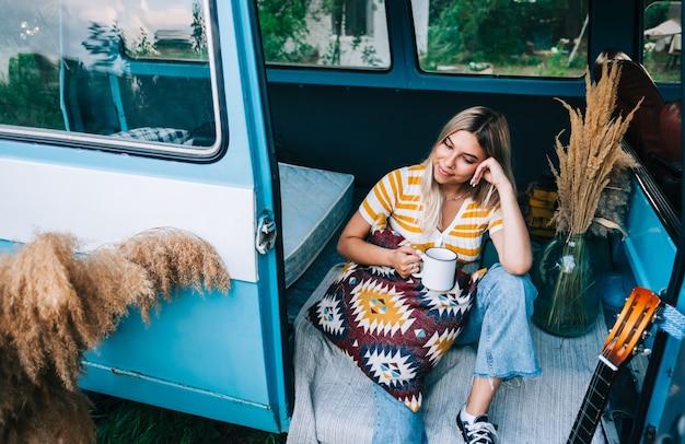 Portrait d'une jeune femme heureuse assise dans une camionnette et buvant du thé à l'extérieur dans la nature, pendant le coucher du soleil. profiter de l'été, concept de voyage