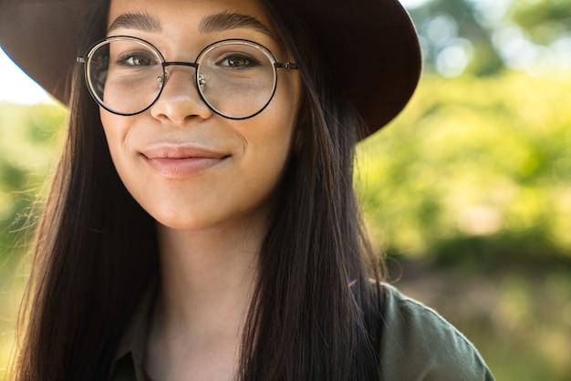 Portrait d'une jeune femme heureuse aux longs cheveux noirs portant un chapeau élégant et des lunettes marchant dans un parc verdoyant par une journée ensoleillée
