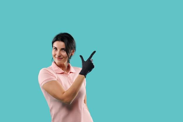 Portrait de jeune femme heureuse debout isolé sur fond bleu. à la caméra en pointant son doigt vers le haut montrant un espace de copie pour les promotions
